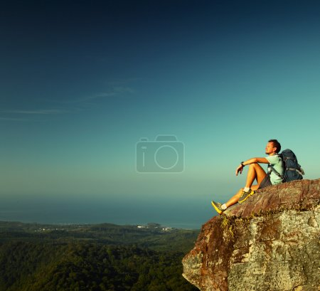 Photo for Male hiker with backpack relaxing on top of a mountain - Royalty Free Image