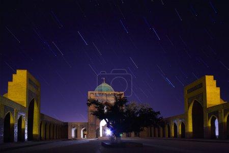 Photo pour Yard intérieure de la madrasa du complexe oriental de poi kalyan nuit avec des traînées d'étoiles. Boukhara, Ouzbékistan - image libre de droit