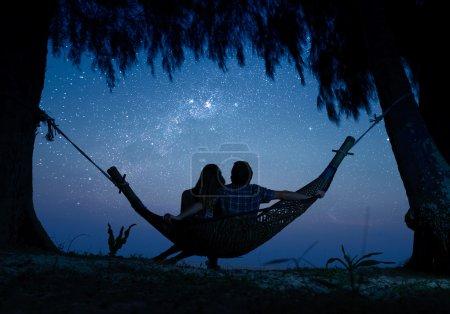 Photo pour Couple délassant dans un hamac et d'apprécier le ciel étoilé - image libre de droit