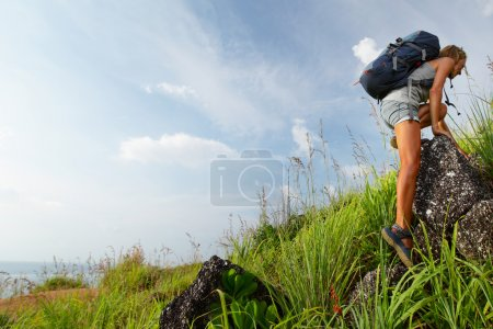 Photo for Tourist with backpack moving through rocky terrain - Royalty Free Image