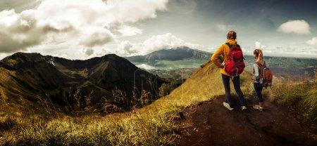 Photo pour Deux dames avec des sacs à dos debout sur le sommet de la montagne et bénéficiant d'une vue sur la vallée - image libre de droit
