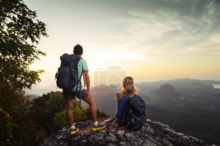 Photo for Two hikers relaxing on top of hill and enjoying sunrise over the valley - Royalty Free Image