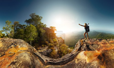 Photo for Hiker standing on top of the mountain with raised hand - Royalty Free Image