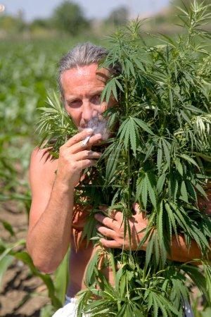 Tanned man smokes a cigarette in the marijuana bra...