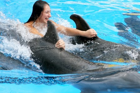 Beautiful young happy girl laughs and swims with dolphins in the
