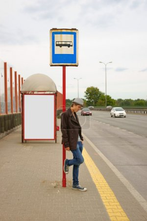 Teen boy standing at a bus stop, in the background billboard advertising