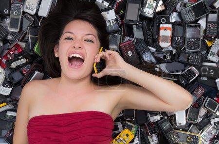 femme sur une pile de téléphones mobiles