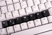 Slovo síť napsané s černými klávesami na klávesnici počítače