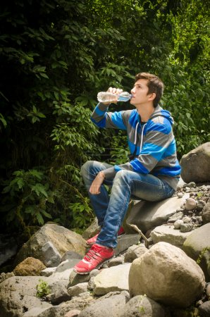 Man drinking water outdoors in the jungle