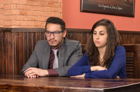 Photo pour Jeune couple dans un restaurant regardant malheureux - image libre de droit