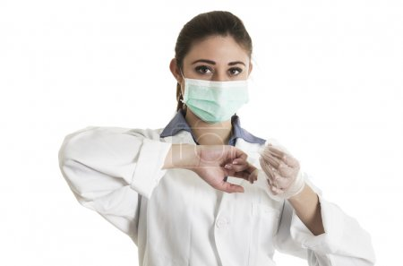 Young female doctor wearing gloves and mask
