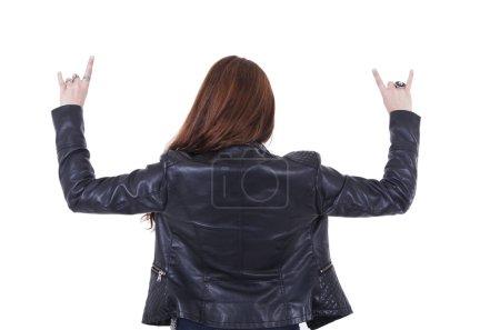 Photo pour Fille de rocker avec roche gesticulant de veste en cuir sur la vue arrière isolé sur blanc - image libre de droit