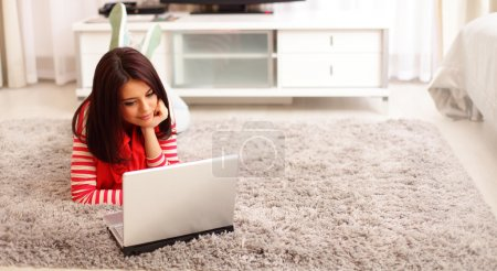 Photo for Portrait of dreamy smiling young woman using laptop while lying on floor at home - Royalty Free Image