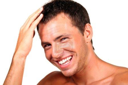 Photo pour Gros plan d'un jeune homme heureux regardant la caméra et de toucher ses cheveux - image libre de droit