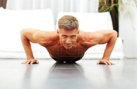 Handsome strong man doing push-ups