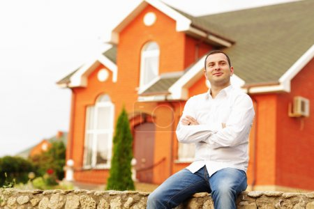 Man in front of his own house.