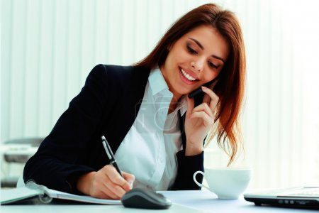 Businesswoman talking on the phone and writing notes