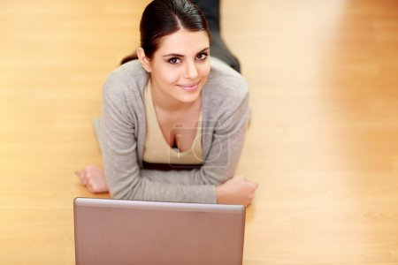 Woman lying on the floor with laptop