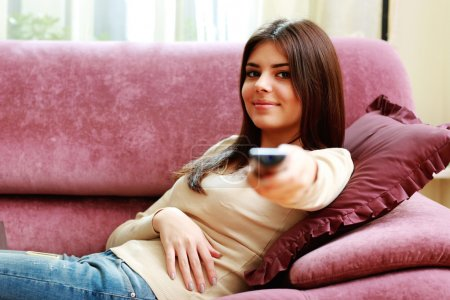 Woman lying on the sofa with remote control