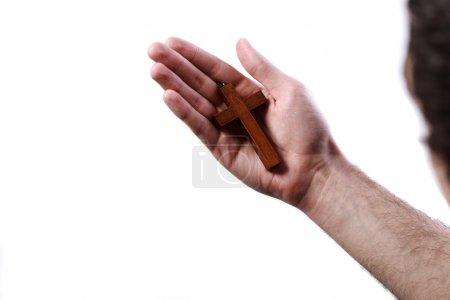 Photo pour Main masculine tenant une croix en bois sur fond blanc - image libre de droit