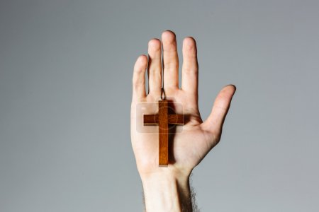 Photo for Male hand holding wooden cross on gray background - Royalty Free Image