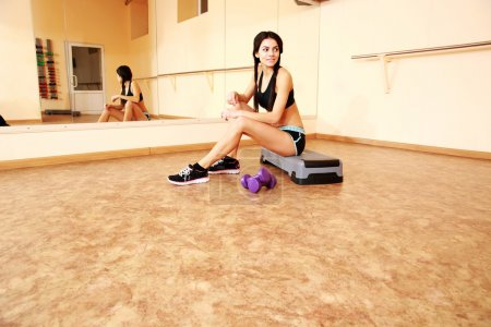 Photo for Young cheerful fit woman sitting on the step board at gym - Royalty Free Image