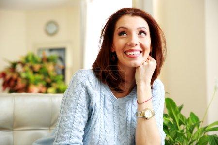 Photo pour Heureuse femme souriante regardant vers le haut à la maison - image libre de droit