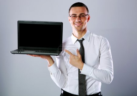 Happy businessman standing with laptop and showing...