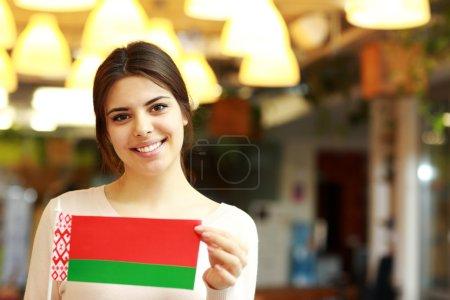 Photo pour Heureuse étudiante tenant le drapeau de Belarus - image libre de droit