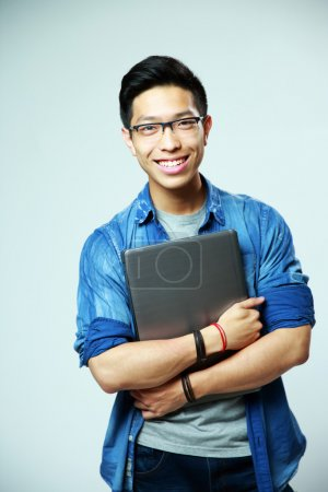 Photo for Happy asian man standing with laptop on gray background - Royalty Free Image