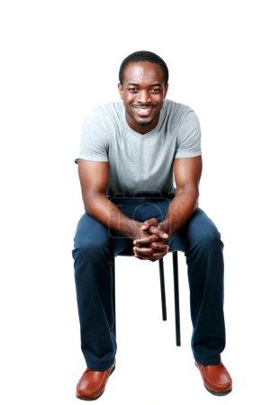 Photo pour Portrait d'un homme africain heureux assis sur la chaise plus bakground blanc - image libre de droit