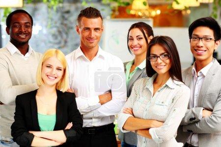 Photo pour Heureux groupe de collègues debout dans le bureau - image libre de droit