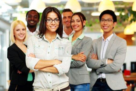 Photo pour Groupe souriant de collègues debout dans le bureau - image libre de droit