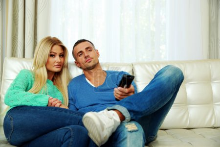 Photo for Lovely young couple sitting on the sofa and watching TV - Royalty Free Image