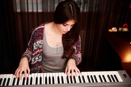 Photo pour Jeune belle femme jouant au piano à la maison - image libre de droit