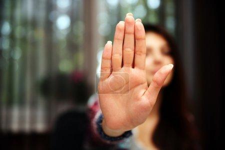 Photo pour Femme avec sa main étendue de signalisation arrêter (seulement sa main est en bref) - image libre de droit