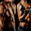 Bodybuilding. Strong man and a woman posing on a b...