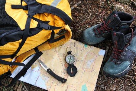 Photo pour Chaussures de randonnée sur la carte avec la boussole et sac à dos - image libre de droit