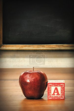 Delicious red apple on school desk