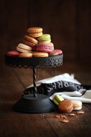 Photo for Metal cake stand with macaroons on dark wood background - Royalty Free Image