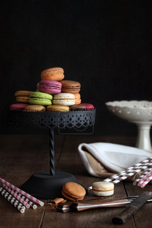 Delicious macaroons on cake stand with dark backgr...