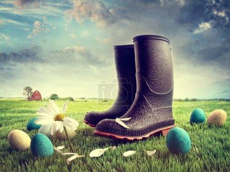 Foto de Botas de goma con huevos de Pascua sobre hierba en el campo - Imagen libre de derechos