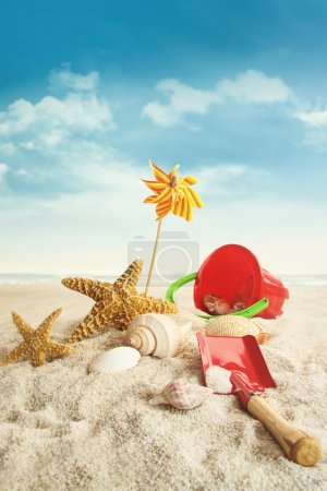 Beach toys on beach against blue sky