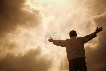 Photo pour Homme et drammatic les nuages, la notion de religion, mise au point sélective - image libre de droit