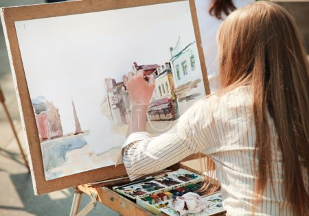 Photo for Young woman painting outside, focus point on hand (selective) - Royalty Free Image