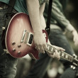 Play on guitar, selective focus on part of hand an...