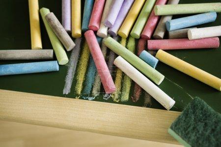 Multicoloured chalks and chalk eraser on the blackboard