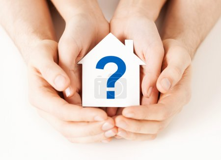 Hands holding house with question mark