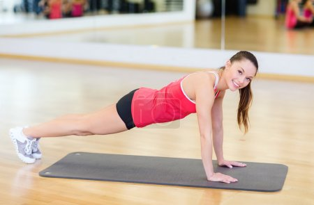 smiling woman doing plank on mat in gym
