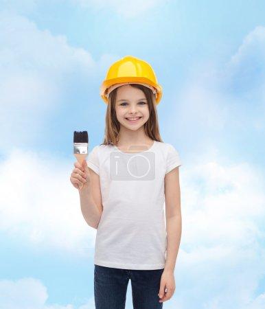 smiling little girl in helmet with paint roller